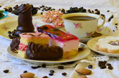 Desserts with cup of coffee, coffee beans and almonds on white tablecloth.  Stock Photo