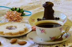 Desserts with cup of coffee, coffee beans and almonds on white tablecloth.  Stock Image