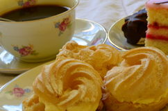 Desserts with cup of coffee on white tablecloth Stock Images