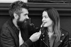 Desserts et concept de temps de déjeuner Le type avec la barbe alimente la fille Photos stock