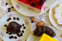 Desserts met kop koffie, koffiebonen en amandelen op wit tafelkleed Stock Afbeeldingen