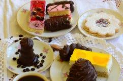 Desserts met kop koffie, koffiebonen en amandelen op wit tafelkleed Stock Fotografie