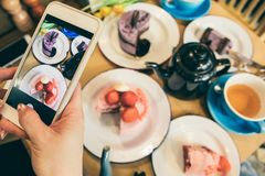 Desserts sweets table mobile food photo with cell phone. Cafe table top view. Cakes and tea time stock photos