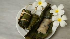 Desserts thaïlandais, lien de gruau, riz collant enveloppé dans des feuilles de banane, remplissage de banane, aliment cuits cuit clips vidéos
