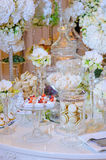Desserts at the wedding table. Pastries, macaroon and meringue with berries on the wedding table with flowers royalty free stock photo