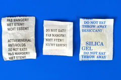 Dessicant, silica gel. Macro of silica gel bags on blue background Royalty Free Stock Photography