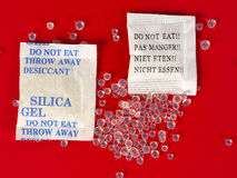 Dessicant, silica gel. Macro of silica gel bags on red background Royalty Free Stock Photography