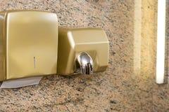 Dessiccateur de papier de distributeur et de main sur le mur dans la toilette publique photographie stock