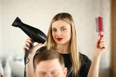 Dessiccateur et peigne blonds de coup d'apparence de styliste en coiffure image stock