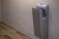Dessiccateur vertical moderne de main dans la carte de travail publique de toilettes Images stock
