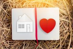 Dessin à la maison doux à la maison de maison avec le coeur rouge sur le carnet Photographie stock