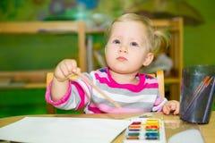 Dessin adorable de fille d'enfant avec les crayons colorés dans la chambre de crèche Enfant dans le jardin d'enfants en classe d' Photo stock