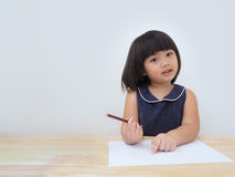 Dessin asiatique heureux de fille d'enfant avec le crayon coloré, enfant apprenant et jouant à la maison images stock