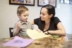 Dessin d'enfant avec sa maman, séance à la table dans la cuisine à la maison image libre de droits