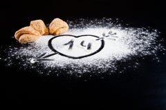 Dessin d'un coeur avec une flèche sur la farine et les biscuits au happin Image stock