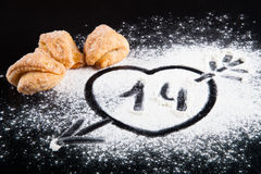 Dessin d'un coeur avec une flèche sur la farine et les biscuits au happin Photo stock