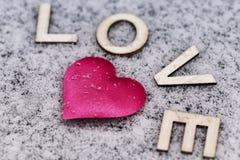 Dessin d'un coeur sur le neigeux Jour du `s de Valentine Coeur de rose dans la neige avec les lettres douces Jour du `s de Valent image libre de droits