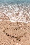 Dessin d'un coeur sur le sable sur la plage et de vague avec la mousse Voyage en mer et vacances Photographie stock