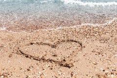 Dessin d'un coeur sur le sable sur la plage et de vague avec la mousse Voyage en mer et vacances Photographie stock libre de droits