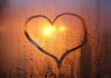 Dessin d'un coeur sur le verre en sueur de la fenêtre Photographie stock