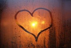 Dessin d'un coeur sur le verre en sueur de la fenêtre Images stock