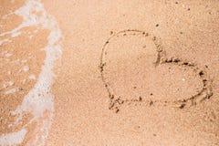 Dessin d'un coeur sur un à sable jaune à un beau fond de paysage marin Photo stock