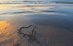 Dessin d'un coeur sur un à sable jaune à un bel endroit de paysage marin Photos libres de droits