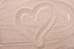 Dessin de coeur sur le sable de mer Photos stock