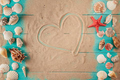 Dessin de coeur sur le sable parmi des coquillages Photographie stock libre de droits