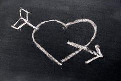 Dessin de craie blanc au coeur avec la forme de flèche sur le conseil noir Photos stock
