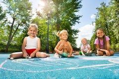 Dessin de craie d'aspiration d'enfants sur le terrain de jeu Photographie stock libre de droits