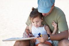 Dessin de famille avec des crayons sur la plage Photo stock