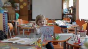 Dessin de fille à la table dans la salle de classe Éducation Enfant s'asseyant à un bureau banque de vidéos