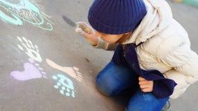 Dessin de fille avec la craie colorée sur le trottoir Image libre de droits