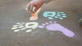 Dessin de fille avec la craie colorée sur le trottoir Images libres de droits