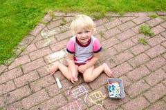 Dessin de fille d'enfant en bas âge avec la craie dehors photos libres de droits