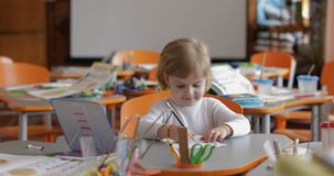 Dessin de fille ? la table dans la salle de classe ?ducation Enfant s'asseyant ? un bureau images stock