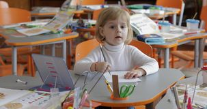 Dessin de fille ? la table dans la salle de classe ?ducation Enfant s'asseyant ? un bureau photos libres de droits