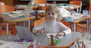 Dessin de fille ? la table dans la salle de classe ?ducation Enfant s'asseyant ? un bureau banque de vidéos