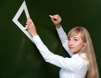 Dessin de fille sur un tableau noir dans la classe Photographie stock