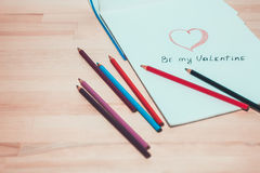 Dessin de forme de coeur sur le livre blanc et les crayons Le jour de Valentine Image stock