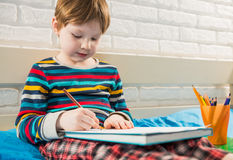 Dessin de garçon avec des crayons Images stock