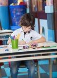 Dessin de garçon avec l'étudiant Sitting In Background Photo stock