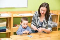 Dessin de garçon de mère et d'enfant ainsi que des crayons de couleur dans l'école maternelle à la table dans le jardin d'enfants Photo stock