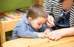 Dessin de garçon de mère et d'enfant ainsi que des crayons de couleur dans l'école maternelle à la table dans le jardin d'enfants Image stock