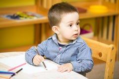 Dessin de garçon de petit enfant avec les crayons colorés dans l'école maternelle à la table dans le jardin d'enfants Photographie stock libre de droits