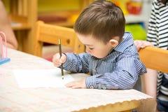 Dessin de garçon de petit enfant avec les crayons colorés dans l'école maternelle à la table dans le jardin d'enfants Photos stock