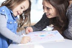 Dessin de mère et de fille dans un livre sur Image stock