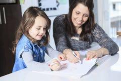 Dessin de mère et de fille dans un livre sur Photo stock