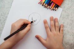 Dessin de main de petit enfant sur le papier photos stock